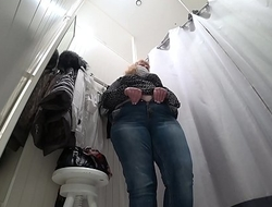 A hidden camera in a public fitting room, a fat milf disguises herself.